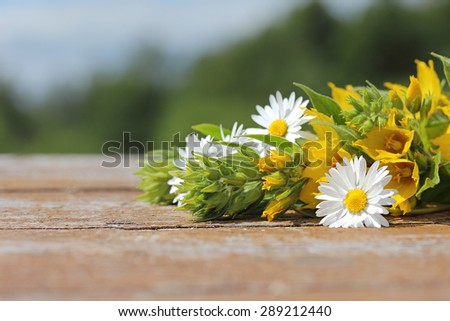Bouquet of wild flowers on the old wooden table against the background of the rural landscape. Background for an inscription. - stock photo