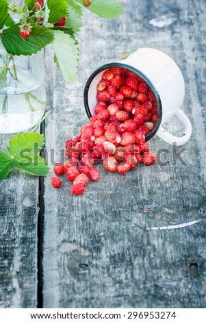 Bouquet of wild strawberries on a rural texture. glass were scattered berries . there is a place for inscriptions . - stock photo