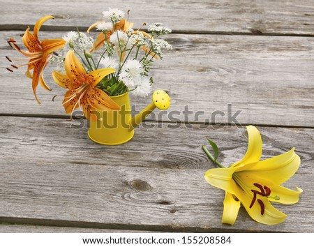 Bouquet of yellow and orange lilies in a watering can on a wooden table - stock photo