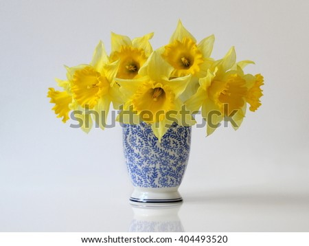 Bouquet of yellow daffodil flowers in a blue vase. Floral home decoration with bouquet of narcissus flowers in a vase. Flower fine art photography. - stock photo