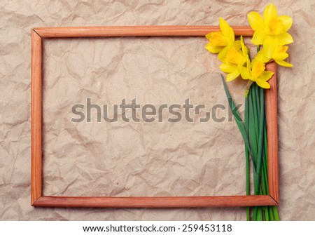 bouquet of yellow daffodils on crumpled paper with space for text in a wooden frame - stock photo