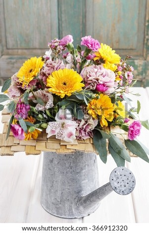 Bouquet of yellow gerbera daisies and pink carnations in silver watering can.  - stock photo