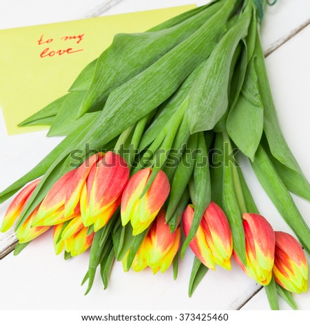 Bouquet of yellow red tulips on  white wooden background. - stock photo