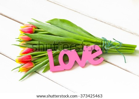 Bouquet of yellow red tulips on  wooden background with Love word.