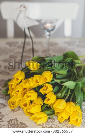 Bouquet of yellow tulips on a table with wooden figure on a background