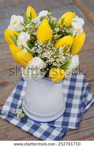 Bouquet of yellow tulips on wooden background, selective focus - stock photo