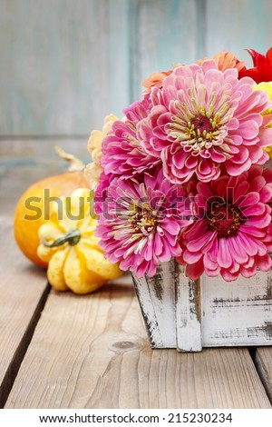 Bouquet of zinnia flowers in wooden box - stock photo