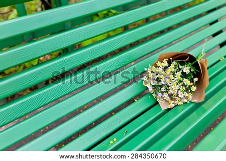 Bouquet on craft paper decoration with daisies in green bench wood background. - stock photo