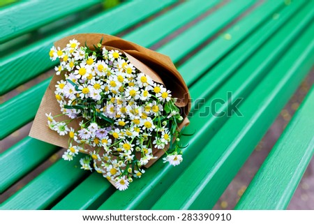 Bouquet on craft paper decoration with daisies in green wood background. - stock photo