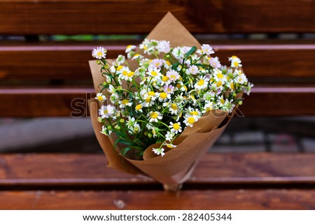 Bouquet  \on craft paper decoration with daisies in vintage wood background. - stock photo