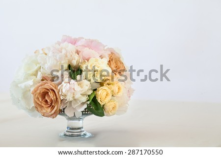 bouquet standing in a vase on a table against the background of bright walls - stock photo