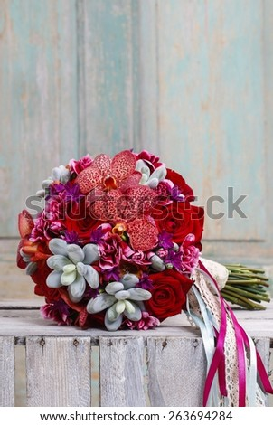 Bouquet with red orchid flowers, roses and succulents - stock photo