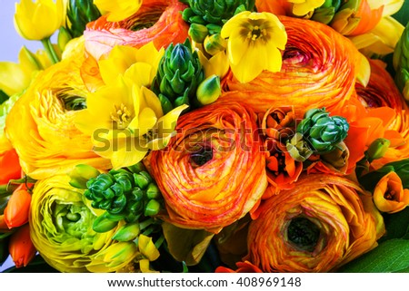Bouquet yellow and orange ranunkulyus with green leaves - stock photo