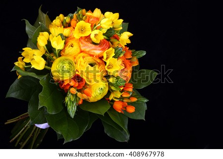 Bouquet yellow ranunkulyus with green leaves on black background  - stock photo