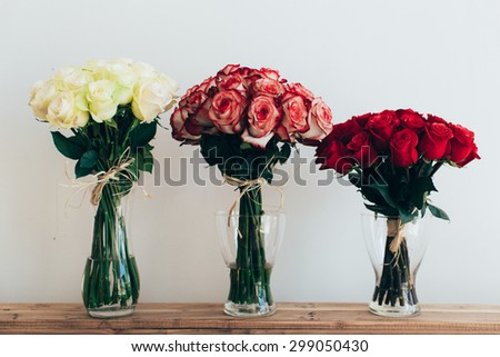 Bouquets of roses in three glass vases next to a watering can on a white wall