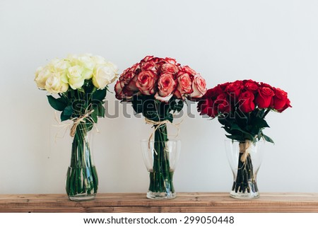Bouquets of roses in three glass vases next to a watering can on a white wall - stock photo
