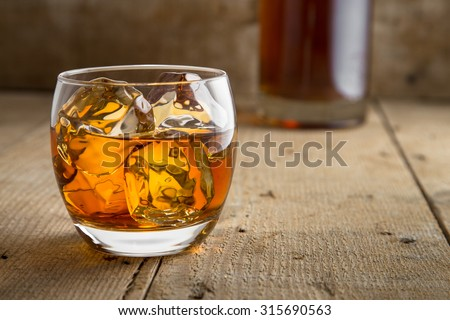 Bourbon brandy and bottle delicious tasty glass on ice classic modern rustic bar table bar saloon barrel