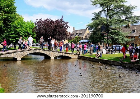 BOURTON ON THE WATER, UK - JUNE 12, 2014 - Tourists crossing a stone footbridge across the River Windrush in the village centre, Bourton on the Water, Gloucestershire, England, UK, June 12, 2014. - stock photo