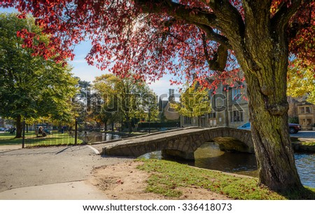 BOURTON ON THE WATER, UK - October 20, 2015 - Stone footbridge across the River Windrush with tea-rooms to the rear, Bourton on the Water, Gloucestershire, England, UK, October 20, 2015