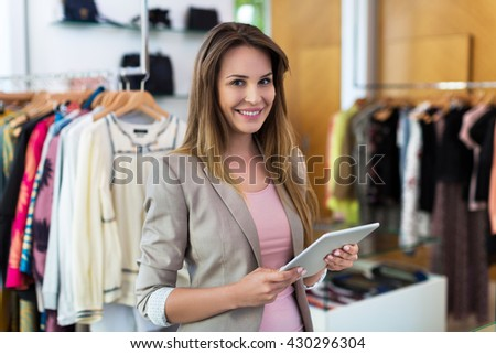 Boutique owner using a digital tablet  - stock photo