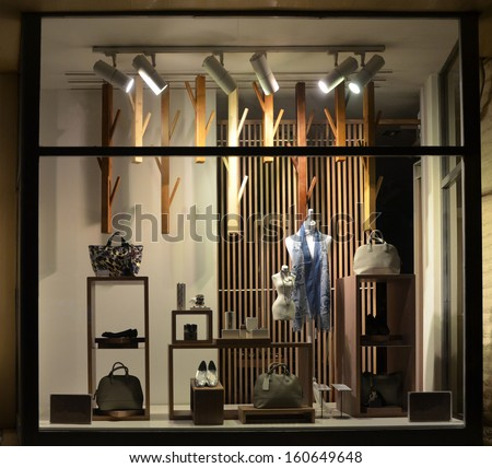 Boutique window with shoes, bags and mannequin - stock photo