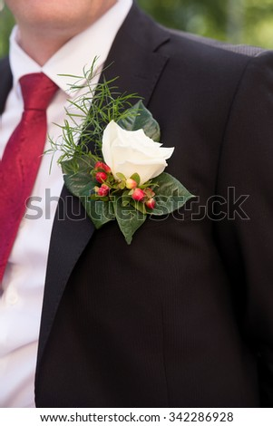 Boutonniere, buttonhole on suit. Groom in wedding day - stock photo