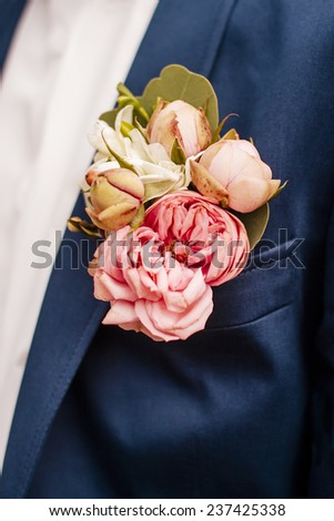 Boutonniere peonies flower on blue suit jacket of wedding groom close-up - stock photo
