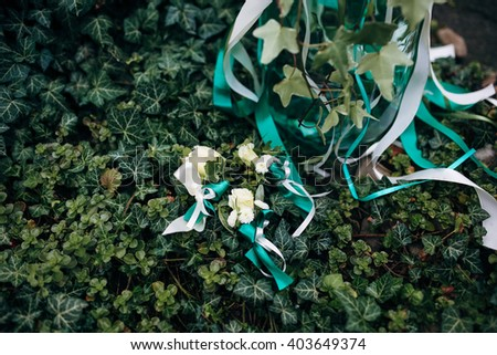 Boutonnieres and the bouquet on the green leaves - stock photo