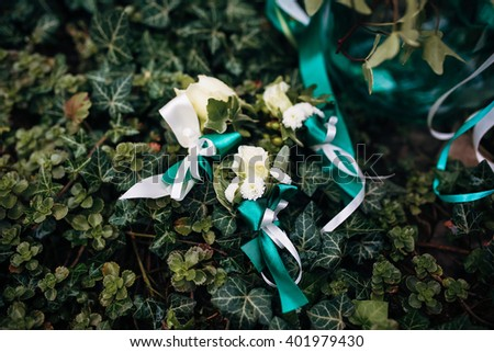 Boutonnieres are lying on the green leaves - stock photo