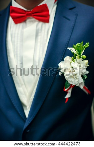 Boutounniere made of white roses and pinned with red ribbon to the blue jacket