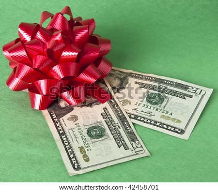 Bow and currency represents the cost of giving gifts during the holidays.