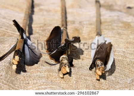 Bow arrows with feathers on gunny sack background
