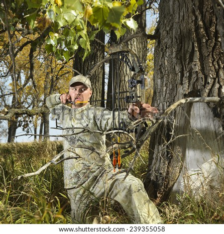 Bow Hunter Aiming Compound Bow in Trees - stock photo