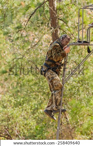 Bow hunter in a ladder style tree stand climbing up to the platform - stock photo