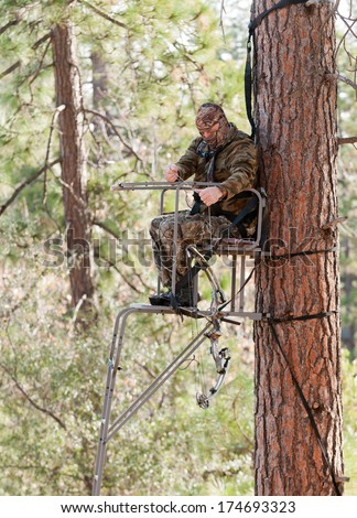 Bow hunter in a ladder style tree stand demonstrating safe practices by using a safety harness and a haul line