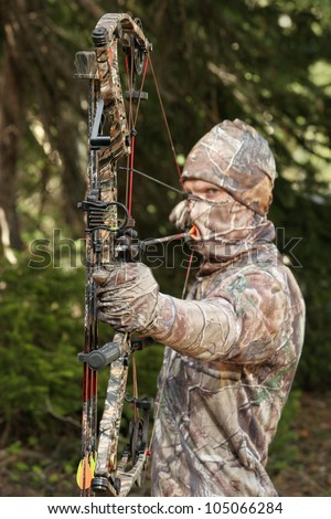 bow hunter in camouflage pulling bow back closeup - stock photo