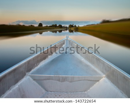 Bow of a Rowing Boat in the Evening with Blurred Background Because of the Movement - stock photo