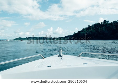 Bow of speed boat heading in the sea - soft focus with film filter - stock photo