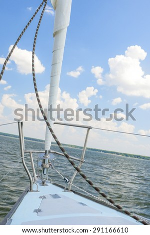 Bow of the Small Yacht Under Sailing On Open Waters. Vertical Image Orientation - stock photo