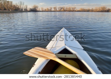 bow of white canoe with wooden paddle on a calm lake in Colorado