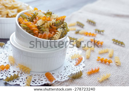 Bow tie pasta in mason jar on wooden board - stock photo