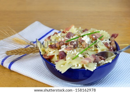 Bow-tie pasta with bacon and cottage cheese in a bowl. Shallow DOF. - stock photo