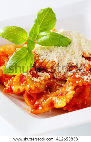Bow-tie pasta with thick tomato sauce and parmesan - stock photo