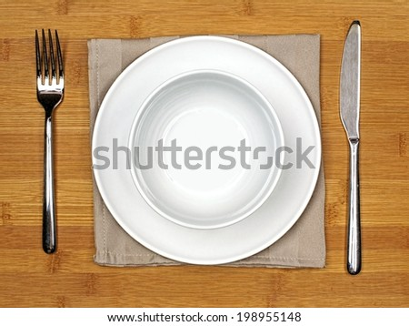 Bowl and plate with fork, knife and napkin on a bamboo wood background - stock photo