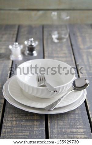 Bowl and plates with spoon and fork, salt and pepper and glass on wooden background - stock photo