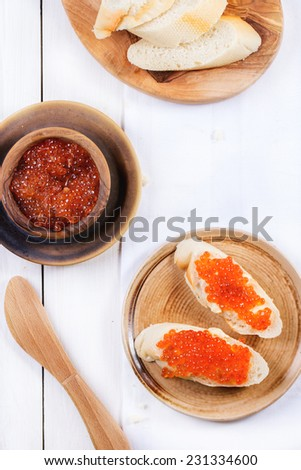 Bowl and sandwiches with red caviar served on ceramic plate over white table. Top view. See series - stock photo