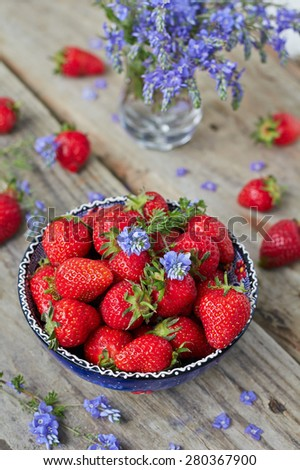 Bowl filled with  juicy fresh ripe red strawberries on an old wooden textured table top - stock photo
