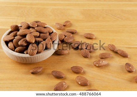 bowl full of almonds on a wooden board