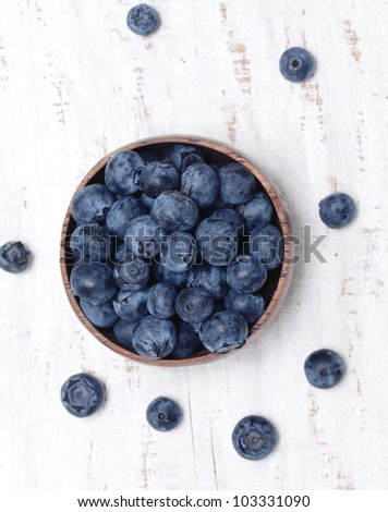 bowl full of blueberries on wooden table - stock photo