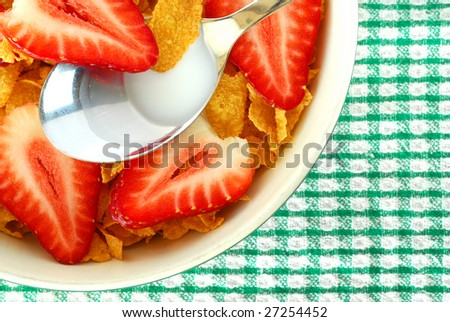 Bowl full of cereal with strawberries and milk